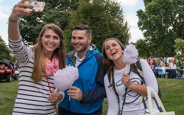 Counselors on campus eating cotton candy taking a selfie