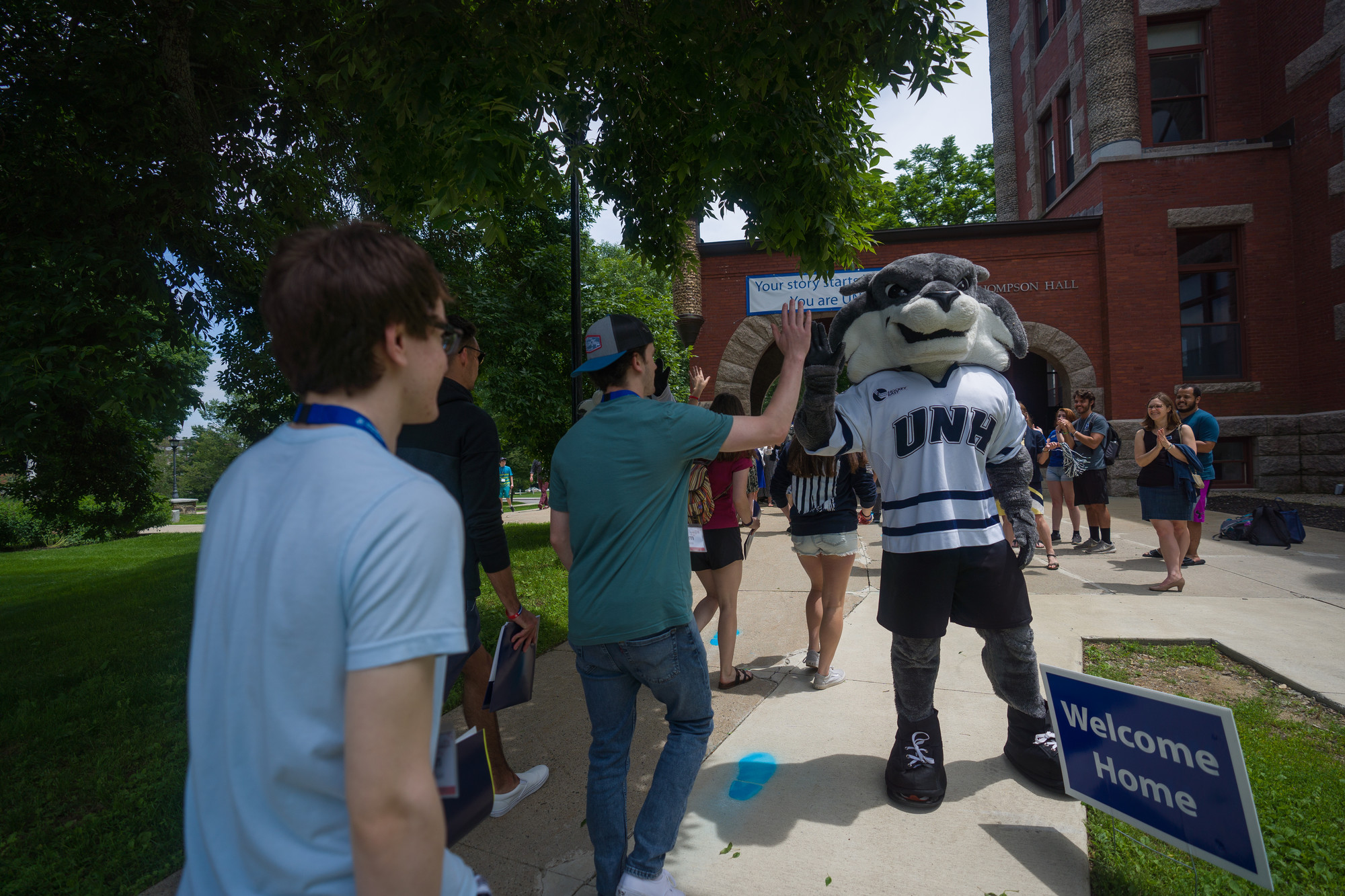 Students at orientation high-fiving the UNH mascot.