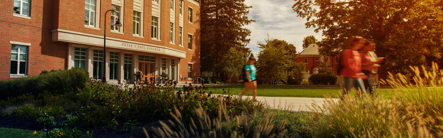 UNH students strolling outside the Peter T. Paul College building