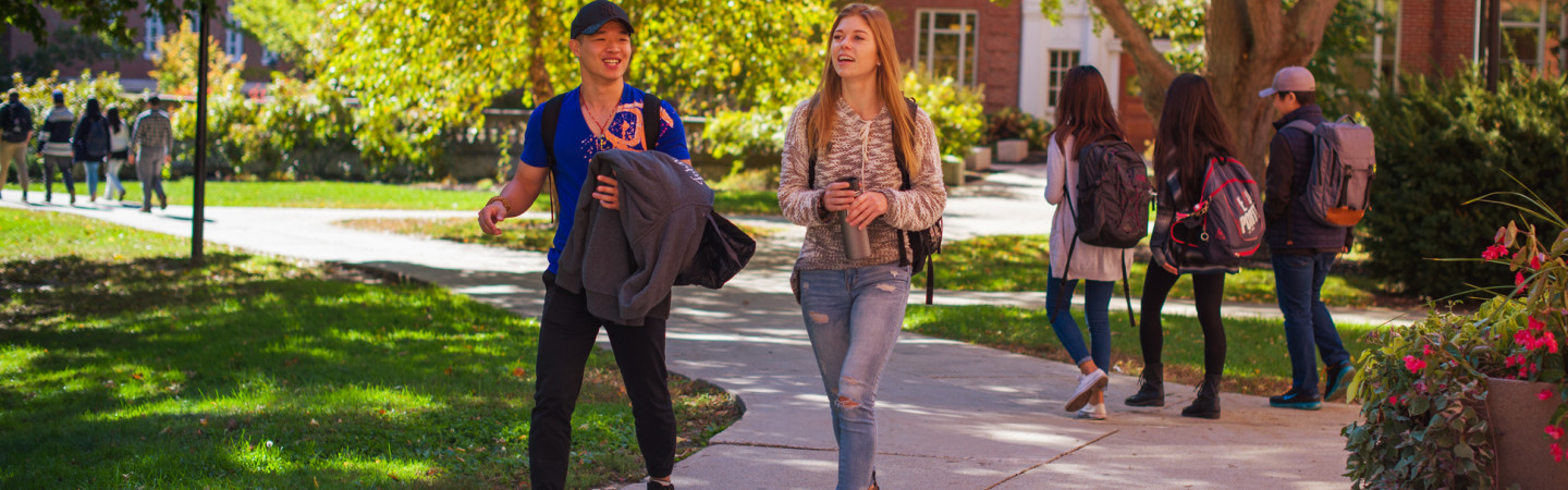 Male and female student walking on campus